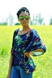 La ragazza afroamericana con i dreadlocks, occhiali da sole d'uso, stanti in un campo dei fiori gialli su un fnd del giorno soleg Immagini Stock