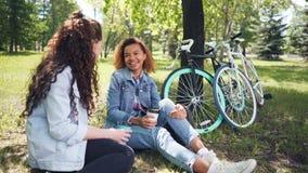 La ragazza afroamericana graziosa sta bevendo il caffè in parco con il suo amico caucasico che si siede sull'erba e sulla risata archivi video