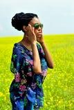 La ragazza afroamericana sta con le sue mani sul campo con i fiori gialli e distoglie lo sguardo Immagine Stock Libera da Diritti