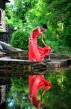 La ragazza afroamericana in un vestito rosso con le scarpe rosse a disposizione vale di estate sull'acqua sulle pietre nel parco Fotografie Stock Libere da Diritti