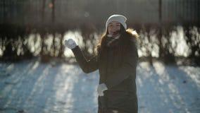 La ragazza agitata felice sta gettando la neve alla macchina fotografica divertendosi all'aperto in Sunny Morning freddo Donna at archivi video