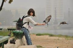 La ragazza alimenta i piccioni, sorridenti Fotografie Stock