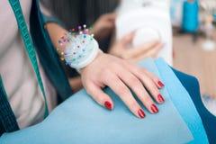 La ragazza alla fabbrica dell'indumento sta scegliendo il materiale per il nuovo vestito fotografie stock libere da diritti