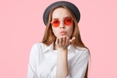 La ragazza alla moda adorabile dei pantaloni a vita bassa indossa le tonalità rosa d'avanguardia e black hat, soffia il bacio del immagine stock libera da diritti