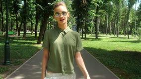 La ragazza alla moda cammina nel parco stock footage