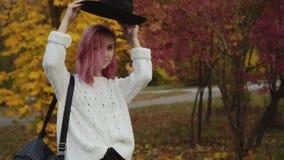 La ragazza alla moda cammina nel parco colourful di autunno, mette sopra il cappello ed i sorrisi video d archivio