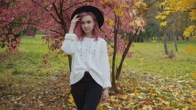 La ragazza alla moda con capelli rosa nelle passeggiate del cappello alla macchina fotografica, corregge i capelli in parco stock footage