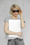 La ragazza alla moda dei pantaloni a vita bassa indossa gli occhiali da sole e tiene il computer portatile a luce del giorno Immagine Stock