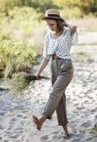 La ragazza alla moda dell'adolescente cammina a piedi nudi nella sabbia Immagini Stock Libere da Diritti