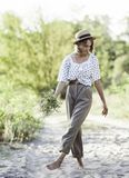 La ragazza alla moda dell'adolescente in pantaloni leggeri rotolati cammina a piedi nudi sulla sabbia Immagini Stock