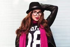 La ragazza alla moda della città in occhiali da sole mostra uno sguardo alla moda Fotografia Stock