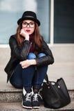 La ragazza alla moda della città in occhiali da sole si siede sui punti Fotografie Stock