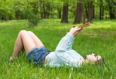 La ragazza alla moda dello studente si rilassa con il libro nel bello parco dell'estate al giorno soleggiato Immagine all'aperto  Fotografia Stock