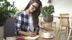 La ragazza alla moda scrive nel diario in caffè stock footage