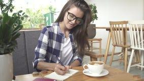 La ragazza alla moda scrive nel giornale in caffè video d archivio