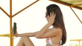 La ragazza alla moda si siede sulla spiaggia e fa la foto al vostro telefono stock footage