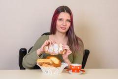 la ragazza alla tavola ottiene un rotolo da un piatto con le pasticcerie fotografia stock libera da diritti