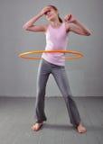 La ragazza allegra adolescente sta facendo gli esercizi con il hula-hoop per sviluppare il muscolo su fondo grigio Divertiresi gi Fotografie Stock