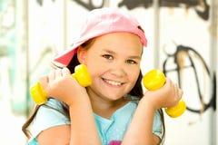 La ragazza allegra adolescente sta facendo gli esercizi con le teste di legno Fotografie Stock
