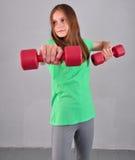 La ragazza allegra adolescente sta facendo gli esercizi con le teste di legno per sviluppare i muscoli su fondo grigio Concetto s Fotografie Stock