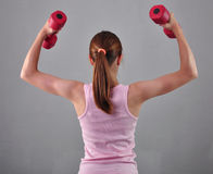 La ragazza allegra adolescente sta facendo gli esercizi per svilupparsi con i muscoli delle teste di legno su fondo grigio Concet Immagine Stock Libera da Diritti