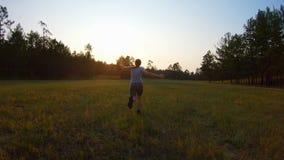 La ragazza allegra, armi ha sollevato correre attraverso il campo al tramonto video d archivio