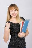 La ragazza allegra con le cartelle in mani che serra il suo pugno nel telaio sorride Immagine Stock Libera da Diritti
