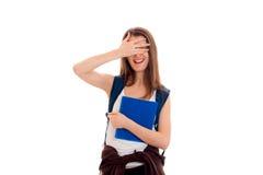 La ragazza allegra con uno zaino sulla vostra tenuta posteriore una cartella e chiude gli occhi con l'altra mano isolata su bianc Fotografia Stock Libera da Diritti