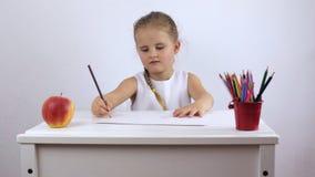 La ragazza allegra disegna un'immagine mentre si siede alla tavola stock footage