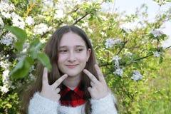 La ragazza allegra e allegra mostra un segno della vittoria con le dita su entrambe le mani su un fondo vago molle di un giardino immagini stock libere da diritti