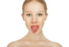 La ragazza allegra mostra la linguetta Immagini Stock