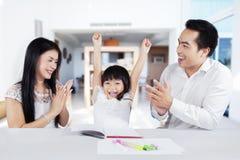 La ragazza allegra ottiene l'apprezzamento dai suoi genitori Immagini Stock