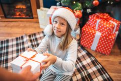 La ragazza allegra prende la scatola con il regalo e gli sguardi all'adulto che lo dà lei Sorride un pezzo La ragazza è riconosce immagine stock libera da diritti