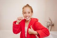 La ragazza allegra pulisce i denti in un bagno Fotografia Stock Libera da Diritti