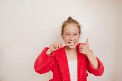 La ragazza allegra pulisce i denti in un bagno Fotografie Stock Libere da Diritti