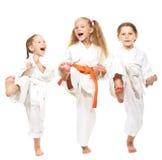 La ragazza allegra tre su un fondo bianco in kimono esegue una gamba della perforazione Fotografia Stock