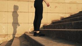 La ragazza allunga i muscoli dei piedi prima della formazione Una ragazza ha allungato i muscoli della gamba prima di un allename