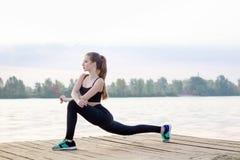 La ragazza allunga le sue gambe durante gli esercizi di allenamento di addestramento Fotografia Stock