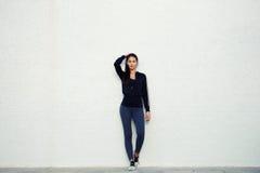 La ragazza alta in abiti sportivi che stanno su un fondo bianco Fotografia Stock