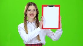 La ragazza alza una compressa rossa con carta Schermo verde archivi video