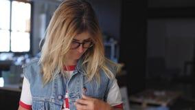La ragazza americana bionda mette un perno sul suo rivestimento stock footage