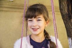 La ragazza 10 anni con un sorriso di estate su un villaggio oscilla fotografia stock