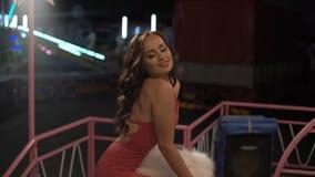 La ragazza appassionata in vestito rosso si appoggia il recinto e la posa delle sue natiche 4K video d archivio