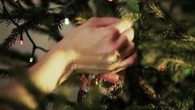 La ragazza appende la decorazione riguarda l'albero di Natale stock footage