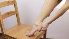 La ragazza applica la crema sullo stinco e sul piede, facenti il massaggio archivi video