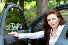 La ragazza apre la porta che esce l'automobile Fotografie Stock