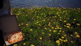 La ragazza apre la scatola di cartone con pizza sul litorale archivi video