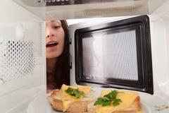 La ragazza apre una microonda Fotografie Stock Libere da Diritti