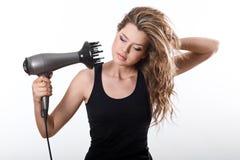 La ragazza asciuga i capelli lunghi con hairdryer Fotografia Stock Libera da Diritti