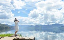 La ragazza ascolta musica che sta sulla piattaforma sulla spiaggia Fotografia Stock